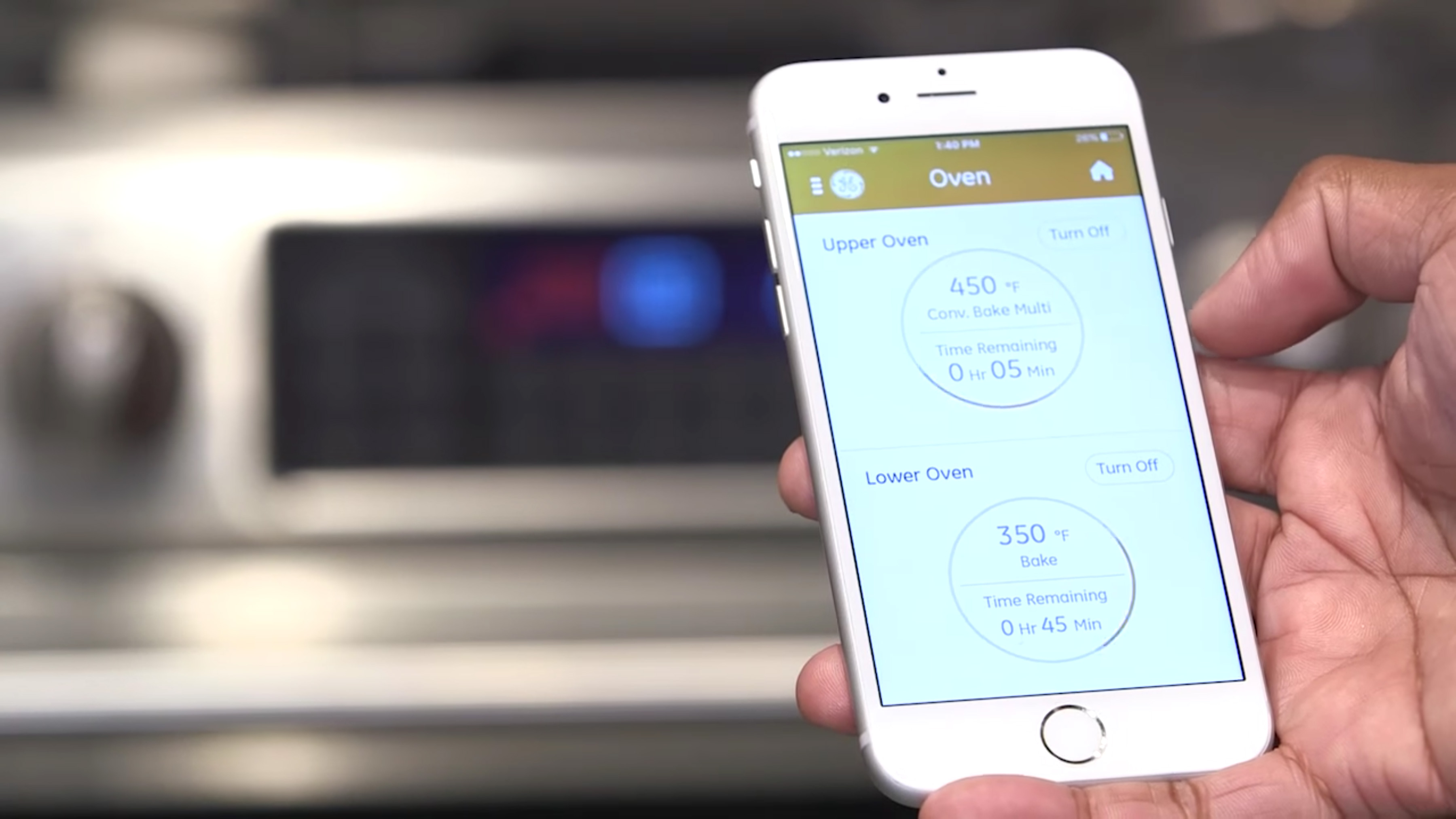 Phone in persons hand with GE Appliances Kitchen App on screen