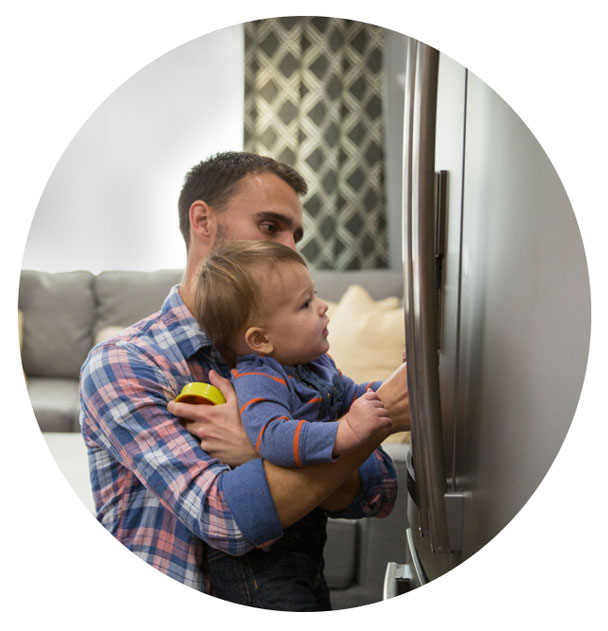 Father with baby standing in front of GE Appliances referigerator